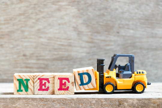 Toy forklift hold letter block D to complete word need on wood background