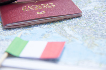 Adventure concept. Sunglasses, small Italy flag and passport on map