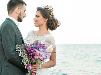 Wedding bride and groom with bouquet posing near sea on sunset
