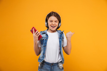 Portrait of an excited little schoolgirl listening to music