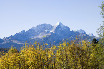 Scenic view of forest and snowcapped mountain in Bavarian alps, Alpspitz, Wetterstein Mountain, Bavaria, Germany