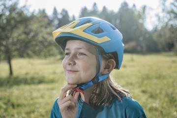 Little girl fixing her Bike helmet , Bavaria, Germany