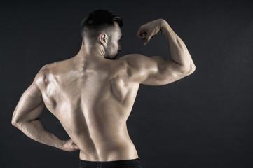Rear view of shirtless man flexing bicep