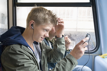 Boy tunes up his hair in public bus, London, England