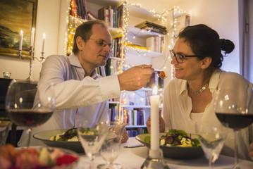 Man feeding woman on a candlelight dinner
