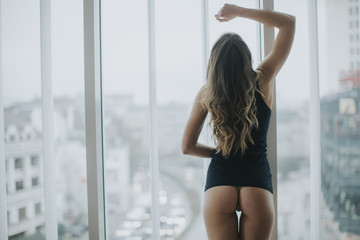 Young woman in underwear standing by window in the room Wall mural