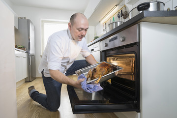 Cook taking Christmas poultry out of oven in the kitchen