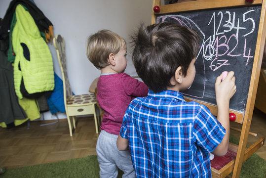 Brothers writing on a blackboard, Munich, Germany