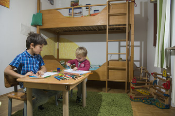 Little boy cutting a paper with scissor while older brother watches him, Munich, Germany