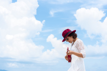 Photo of left side women wearing white dress, red hat playing ukulele outdoor with blue sky and white clouds background. Travel and summer concept.
