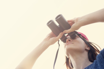 Girl with the binoculars  against the sky. Observation of birds. Birdwatching
