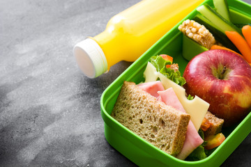 Healthy school lunch box: Sandwich, vegetables ,fruit and juice on black stone. Copyspace