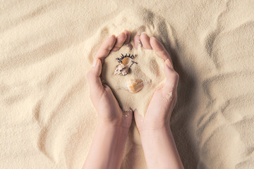 Female hands with sea shells on light sand