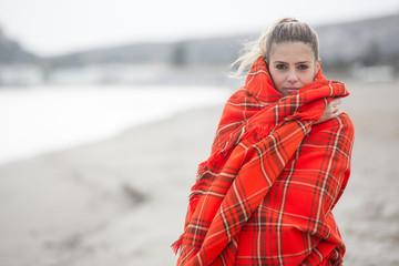 Giovane donna bionda si copre con una coperta a quadri rossa - sfondo spiaggia e mare d'inverno