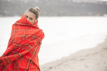 Bella ragazza bionda si copre con una coperta a quadri rossa - sfondo spiaggia e mare d'inverno