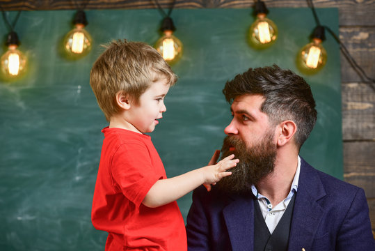 Parenthood concept. Little boy telling something to his dad. Daddy looking at son while kid is playing with his beard. Man and child side view.