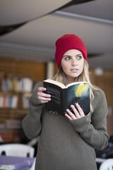 Bellissima ragazza, vestita con un maglione verde e una cuffia rossa tiene in mano un libro che legge e guardalontano