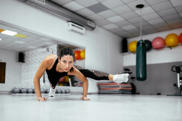 Young woman doing strength training. Looking at camera.