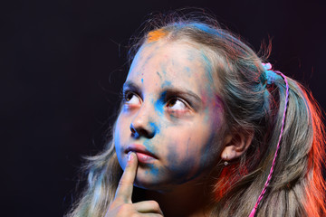 Schoolgirl has paint spots on face. Children and creativity