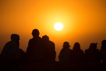 Silhouette einer  Gruppe von jungen Leuten sehen beim Sonnenuntergang zu