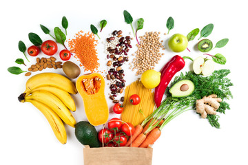 Healthy food background. Healthy vegetarian food in paper bag pasta, vegetables and fruits on white. Shopping food concept. Top view