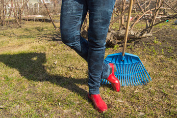 Close-up of female feet in blue jeans and red rubber boots with rakes, garden work