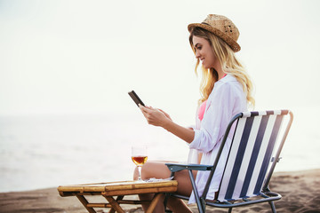 Woman holding tablet computer sitting on the beach in deck chair