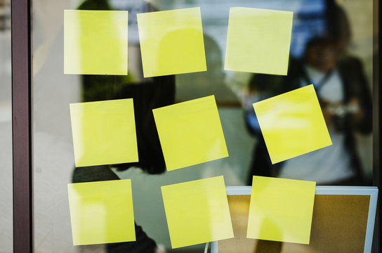 blank yellow sticky note or post note stuck on glass wall.
