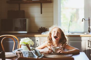 Child girl drinking tea for breakfast in summer country kitchen full of light