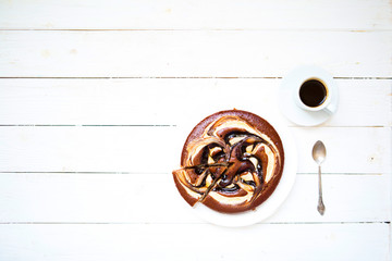 Piece of chokolate cake and cup of coffee on white wooden table. Top view image of restaurant or cafe menu background