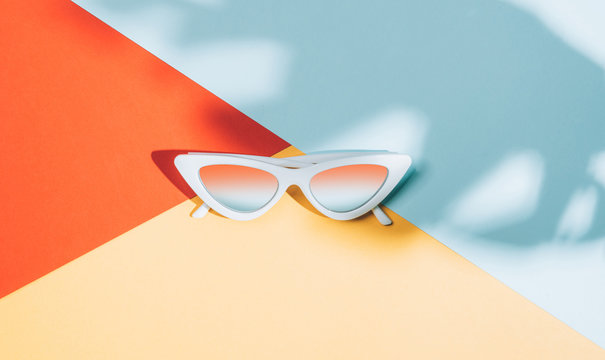 fashionable sunglasses lying on a colored background in the shade of palm trees palm shadow
