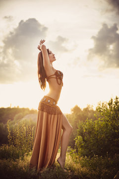 Dancer of bellydance in a gold suit on the background of a canyon. Beautiful nature at sunset. Belly dance. Girl with exotic appearance. Oriental beauty.
