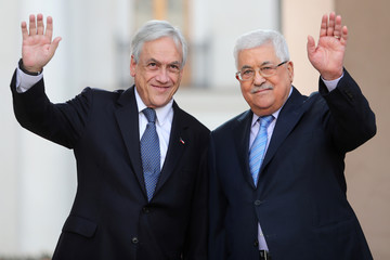 Chile's President Sebastian Pinera and Palestinian President Mahmoud Abbas wave to the media at the government house in Santiago