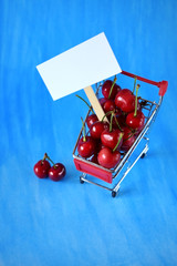 Cherries in a trolley and a white card for text against blue background