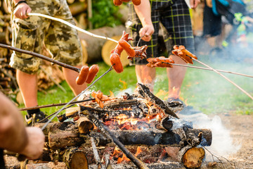 Grilling sausages over a campfire in the forest. Holiday and summer camping in the countryside. Beltaine night in the Czech Republic. May day celebrations.