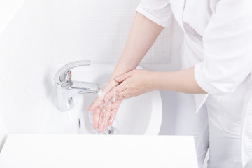 The doctor washes his hands in the treatment room before or after the session. The concept of hygiene and cleanliness