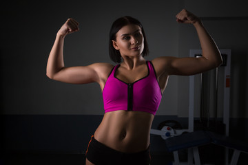 Young strong sexy woman showing her muscles. Halthy concept