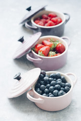 Summer fruit background, top view of berries inside ceramic colored cocotte, blueberries, strawberries, raspberries, flat lay, blue table. Detox and healthy food concept.
