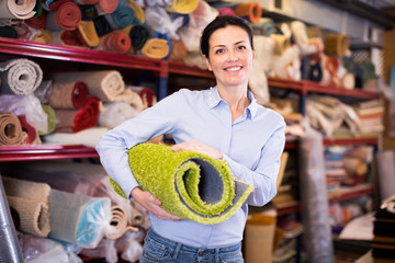 Cheerful woman customer shopping carpet  in store
