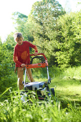 Child boy helping in the garden mowing lawn  with a lawn mower
