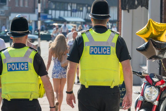 two policemen on the beat in the uk following a pretty girl with long legs and blonde hair