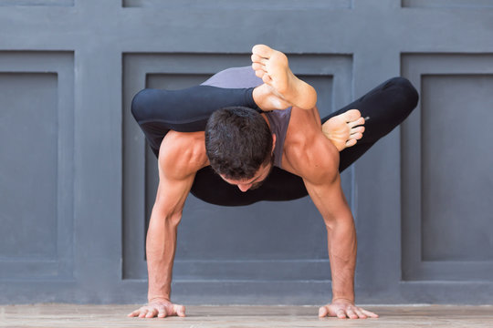 Man doing yoga exercises and practicing handstand balance pose on grey urban background.