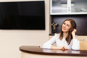 Beautiful female smiling receptionist or secretary at reception in medical clinic or hospital is waiting for patient. Copyspace for text.