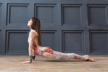 Young woman practicing yoga cobra pose in a studio background