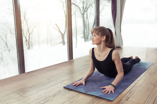 Young woman practicing yoga cobra pose or asana in a nature background near a big windows. rest and yoga in the mountains, snow trees and winter weather concept