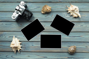 camera, seashells, photo paper with a black background on a blue wooden background. travel, resort.