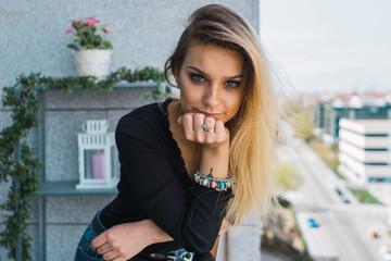 Stylish young woman on balcony