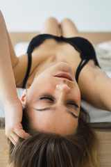 Seductive alluring woman lying on bed