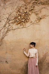 Woman standing at wall with dry foliage