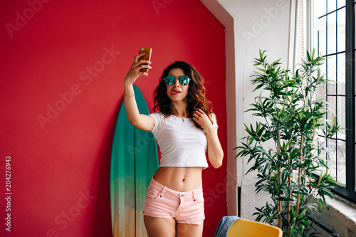 a0cd08b4d542e3 Young brunette in sunglasses posing on a pink background. The girl smiles